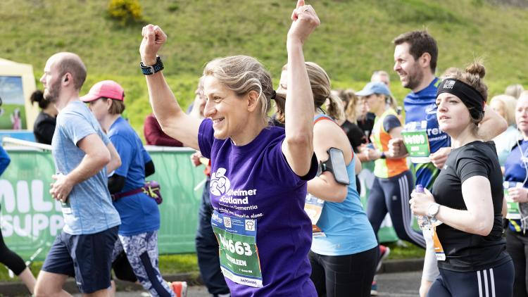 A woman celebrates while running for Alzheimer Scotland