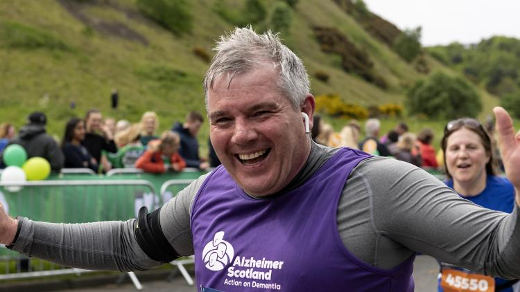 A man cheers running at the Edinburgh Marathon Festival