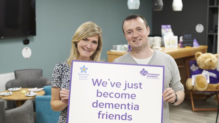 "A woman and man holding a sign that says ""We've just become dementia friends"""