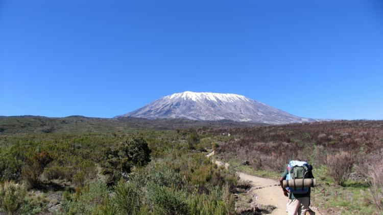 A trekker heads towards Mount Kilimanjaro
