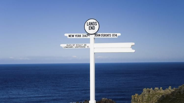 A sign at Lands End displays the distances and direction to New York and John O'Groats