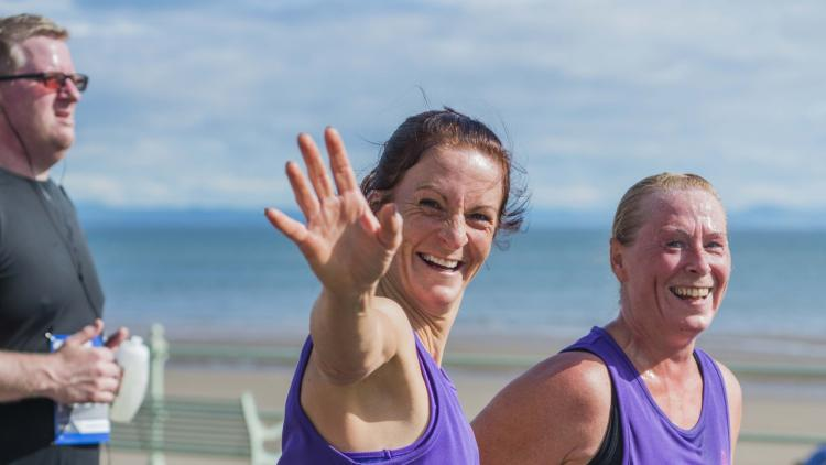 two women wave while running for Alzheimer Scotland