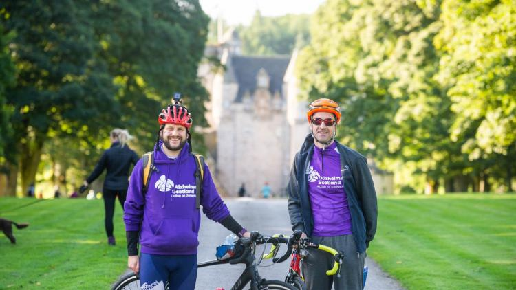 A pair of men beside their bikes smiling, cycling for Alzheimer Scotland